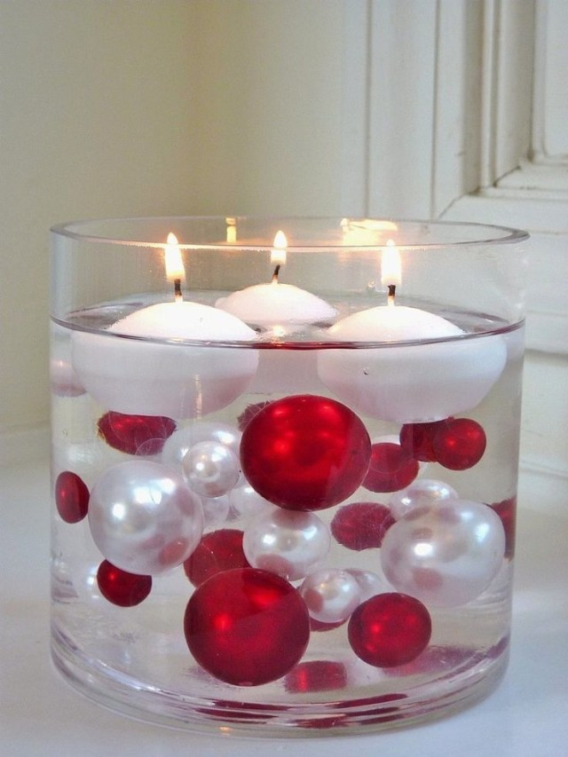 Large glass cylinder with christmas ball ornaments and floating candles.jpg