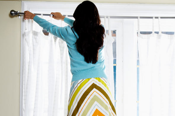Woman hanging curtain rod home 590jn032510.jpg