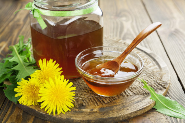 Dandelion jam in a jar on the wooden table