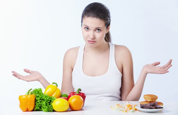 Woman with fruit and junk food on the table.jpg
