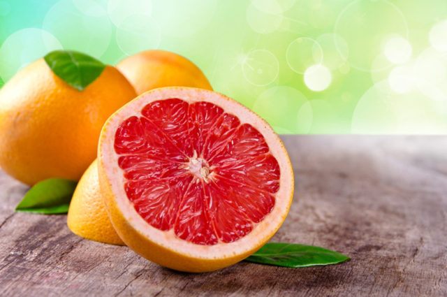 Freshly harvested grapefruit on wooden background