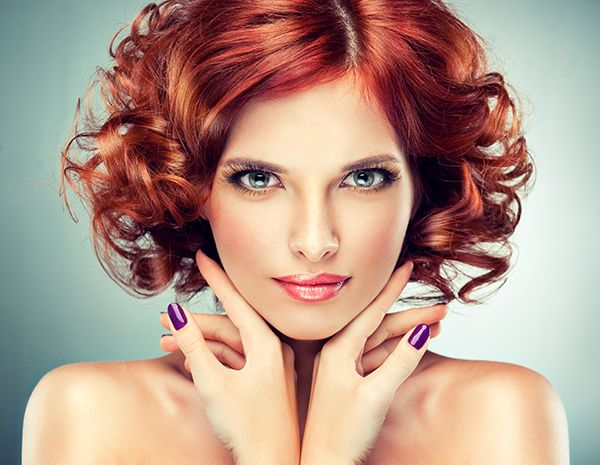 Beautiful model with red curly hair . Fashionable portrait , purple manicure