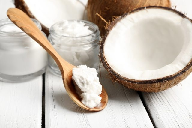 Coconut with jars of coconut oil and cosmetic cream on wooden ba