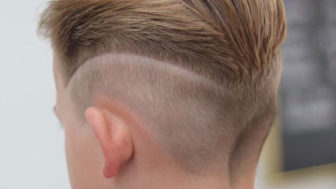 Slicked back hair with mid fade and design.jpg