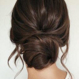 Wedding hairstyles for long hair low simple bun on dark hair with loose curls caraclyne.bridal 334x500.jpg