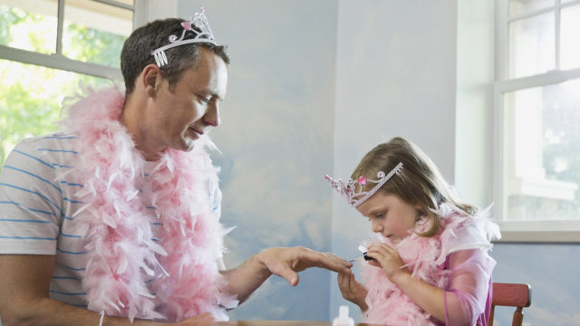 Image: Little girl painting fathers fingernails at table