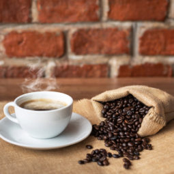 Hot coffee in white cup and roasted coffee beans