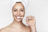 Beautiful young woman brushing teeth, portrait