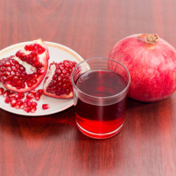 Pomegranate juice in glass, whole and part of split pomegranate