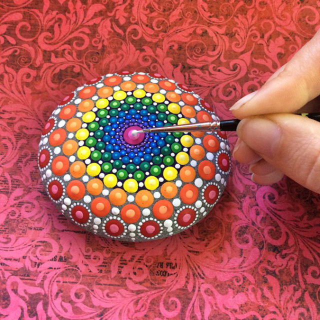 Artist finishes one of her rainbow colored mandala stones.jpeg