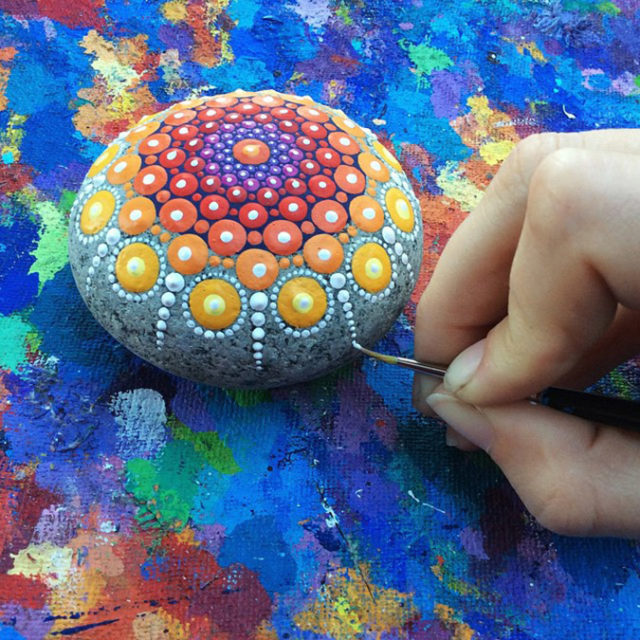 Artist paints one of her mandala stones.jpeg