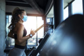 Sportswoman training on treadmill in gym and wearing face mask to protect herself against coronavirus during global pandemic of covid 19 virus.