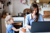 Working mom works from home office. Happy mother and daughter smiling. Successful woman