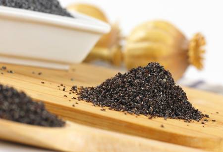 57997882 heap of ground poppy seeds on wooden cutting board.jpg