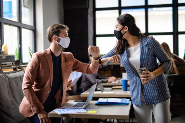 461046_business people with face masks greeting indoors i rmdemtr_edit 676x451.jpg