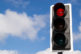 The green streetlight signal with cloudy blue skies in the background.