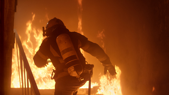 Brave Firefighter Runs Up The Stairs. Raging Fire is Seen Everywhere.