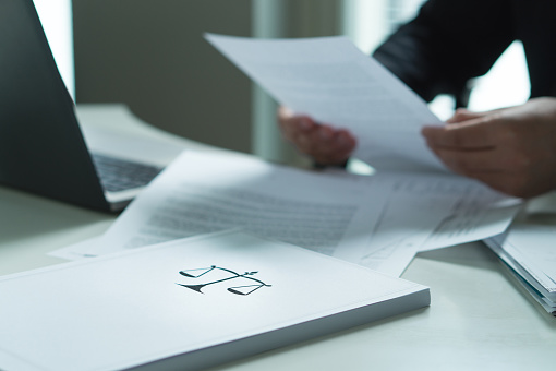 Man holding a legal document in hand. Lawyer holding law paper in office.