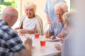 Group of pensioners eating lunch together at the rest home