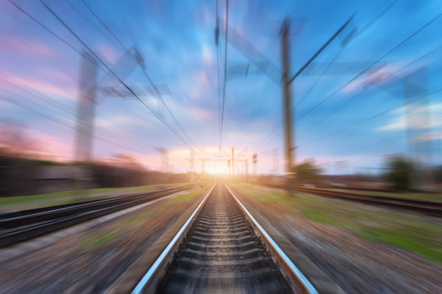 Railway station with motion blur effect at sunset. Blurred railroad. Industrial conceptual landscape with blurred railway station,  blue sky with colorful clouds and sunlight. Railway track.Background
