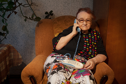 Old woman talking on the home phone sitting in the arm chair in the evening