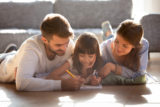 Couple and daughter lying on warm floor and drawing