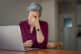 Senior woman suffering headache after work