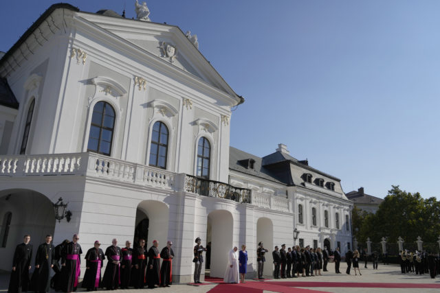 Pope Francis, white figure at center bottom, flanked by Slovakian President Zuzana Caputova, attends a welcoming ceremony at the presidential palace in Bratislava, Slovakia, Monday, Sept. 13, 2021. Francis is on a four-day visit to Central Europe, in Hungary and Slovakia, in his first big international outing since undergoing intestinal surgery in July.