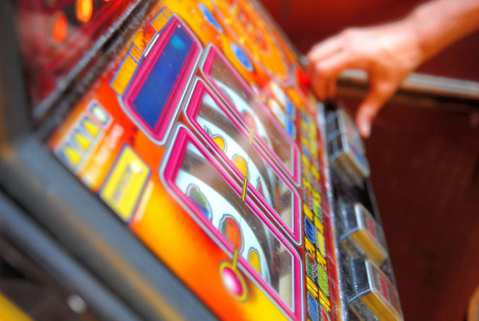 Mid adult playing on gambling machine