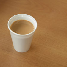 Coffee filled disposable cup on desk, close up
