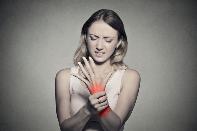 Woman holding her painful wrist