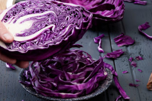 Chopped red cabbage on old wooden table with half cabbage