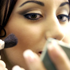 Close up of a young woman putting on makeup