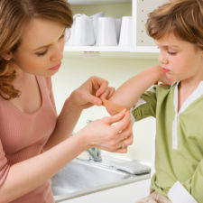Mother putting bandage on daughter's cut