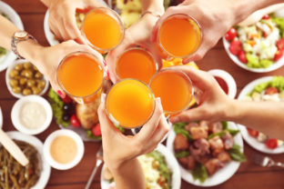 Friends cheering with glasses of orange juice in restaurant