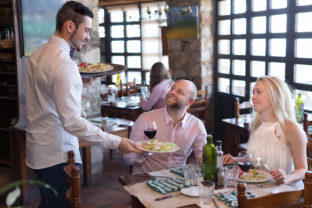 Waiter with restaurant guests at table