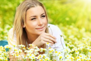 Young beautiful girl laying on the daisy flowers field outdoor portrait small.jpg
