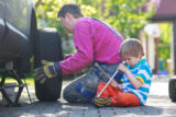 Father with little boy repairing and changing wheel