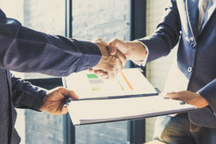 Business partnership meeting concept. Successful businessmen handshaking after good deal and hold financial file. Group support concept.