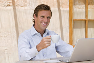 Man with teacup and laptop computer