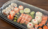 Set of assorted sushi kept in a plastic box on wooden table