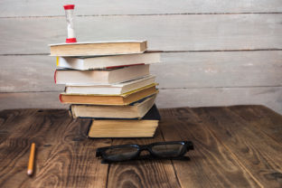 Pile of books and hourglass glasses and pencil