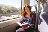 Happy woman in train reading book