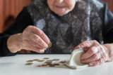 Elderly woman sitting at the table counting money in her wallet.