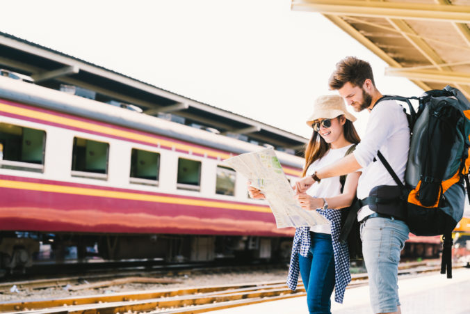 Multiethnic traveler couple, backpacker tourist, or college student using generic local map navigation together at train station platform. Asia tourism trip, outdoor backpack adventure travel concept