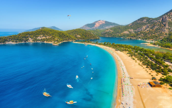 Amazing aerial view of Blue Lagoon in Oludeniz, Turkey. Summer landscape with sea spit, boats and yachts, green trees, azure water, sandy beach in sunny day. Travel. Top view of national park. Nature