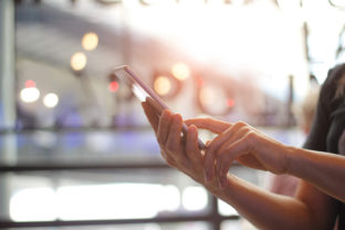 Close up of women's hands holding smartphone. Her watching sms, message, e mail on mobile phone in coffee shop. Blurred background.