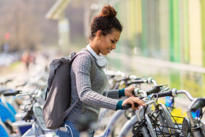 Young woman renting bicycle