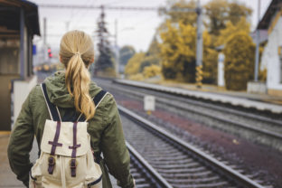 Woman with backpack standing at railroad station platform and waiting for a train. Travel concept.