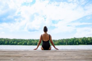 Woman sitting on wooden dock looking at lake in sunny day